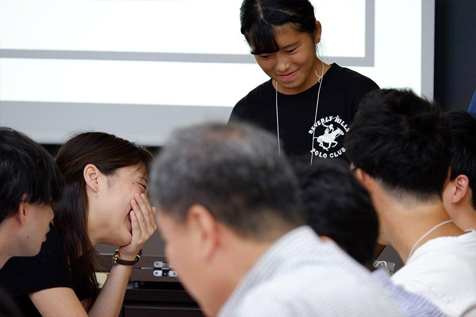写真奥:ファシリテーターの高橋さん、大人相手にも堂々としたファシリテーションを披露した。